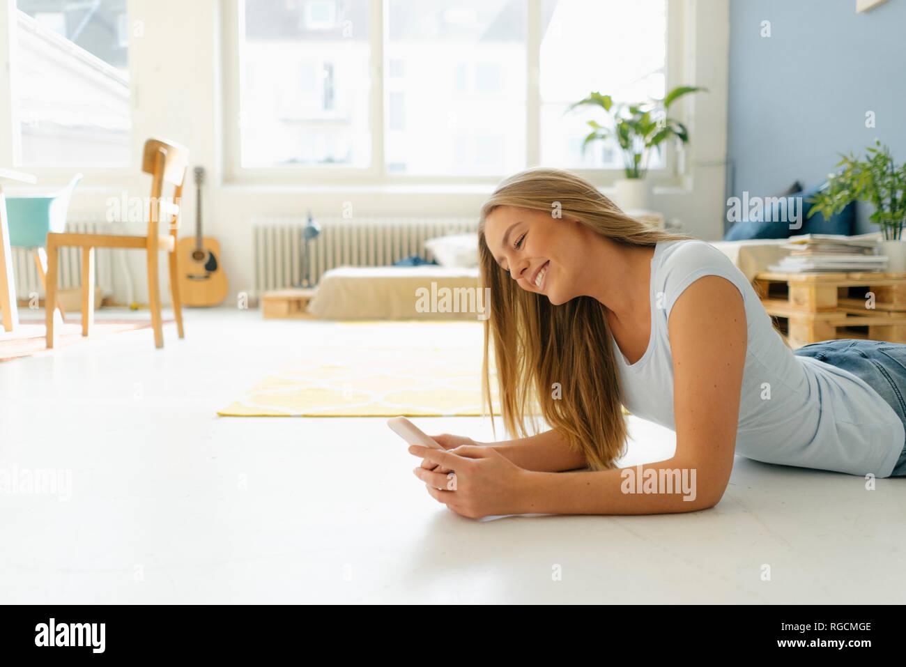 Mujer sonriente tumbado en el suelo en su loft mirando teléfono celular Foto de stock