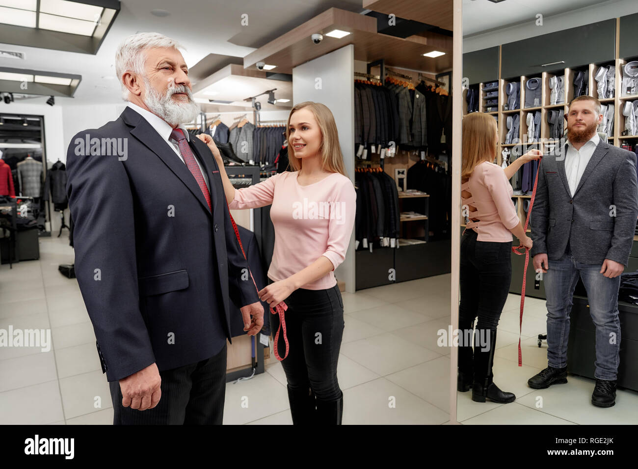 d747f96957 Boutique con ropa de hombre. Anciano tratando de traje clásico en tienda de  ropa cara.