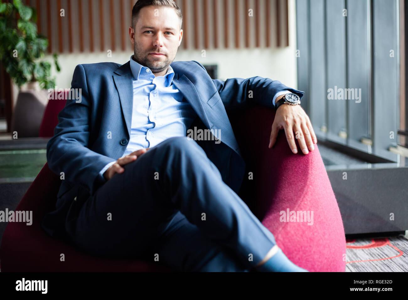 Disfrute cada día de su vida. Empresario positivo sentado en el sofá mientras descansa en la oficina, guapo tiene una rotura en el vestíbulo del hotel. Imagen De Stock