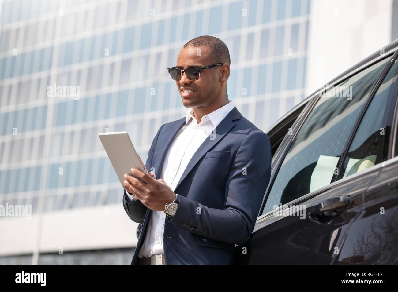 c4d39ca9fe Mulato joven empresario con gafas de sol de pie apoyándose en coche navegar  por internet sobre