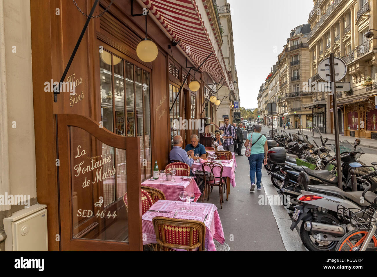 Gente sentada en una mesa comiendo en La Fontaine de Mars, un restaurante francés en Rue Saint-Dominique, París, Francia Foto de stock