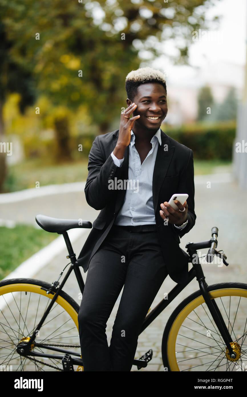 Apuesto joven hombre vestido con traje africano habla por teléfono mientras camina con bicicleta al trabajo por la mañana. El empresario va a trabajar con su bicicleta. Foto de stock