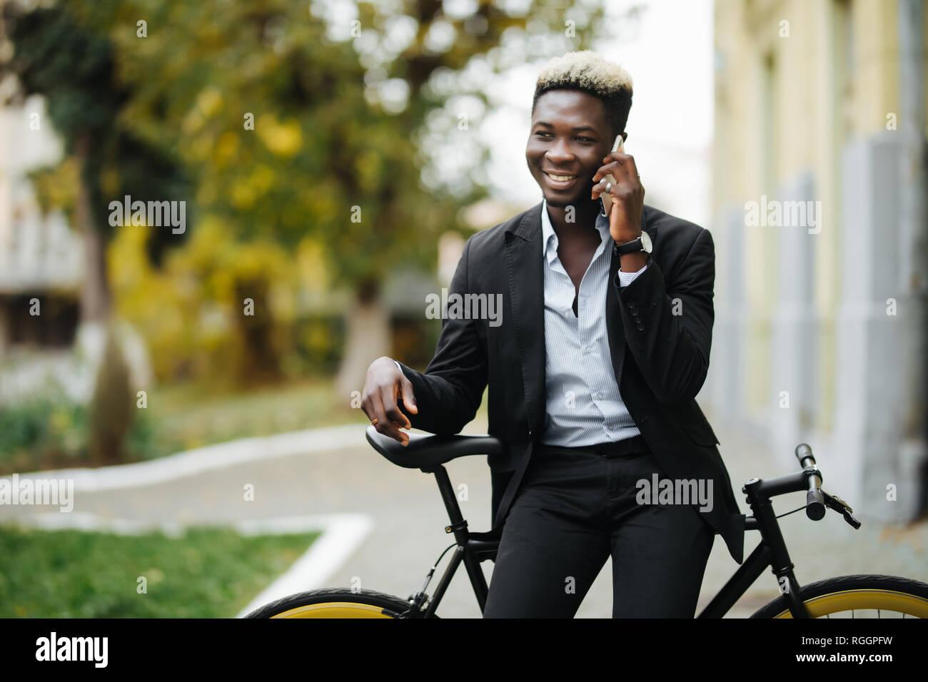 Retrato de un joven apuesto a través de teléfono móvil y el piñón fijo de bicicleta en la calle. Foto de stock
