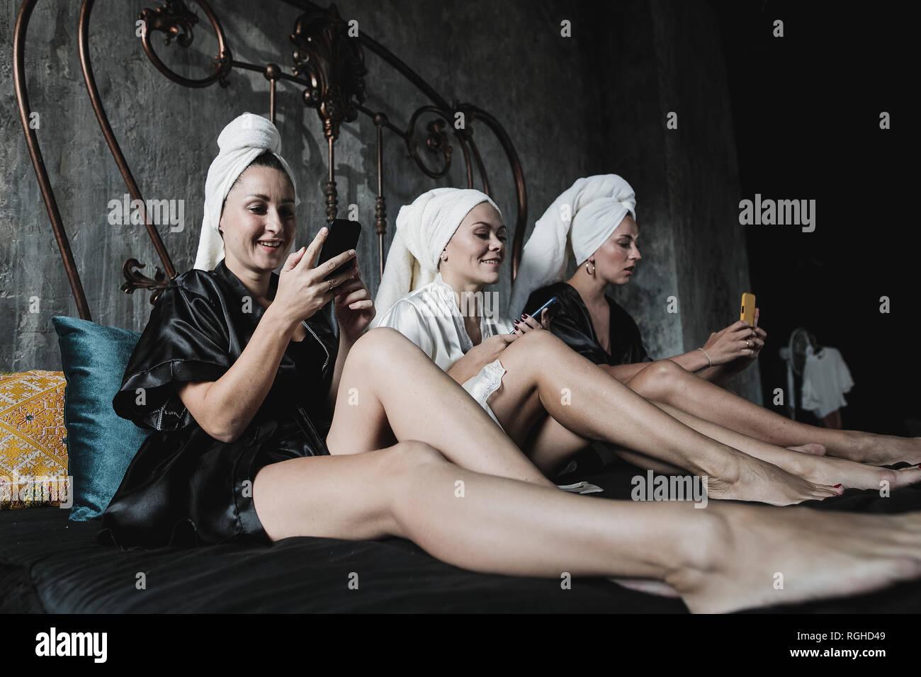 Tres mujeres con toallas alrededor de su cabeza en la cama usando celulares Foto de stock