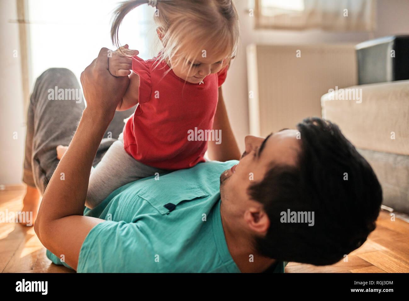 Niña jugando con su padre en casa Foto de stock