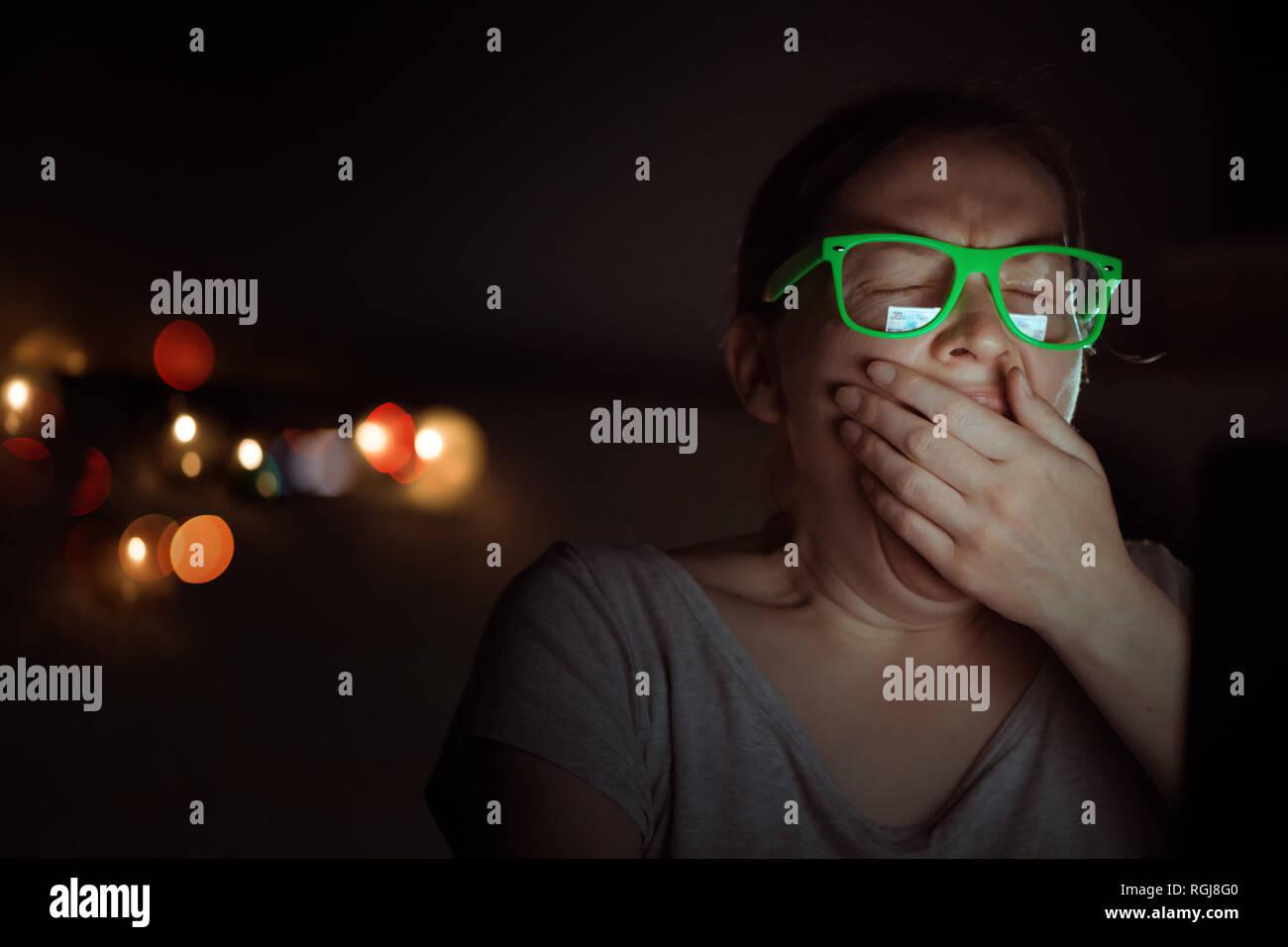 Cansado agotado freelancer mujer está trabajando en equipo portátil y bostezar durante la noche en su oficina en casa Foto de stock