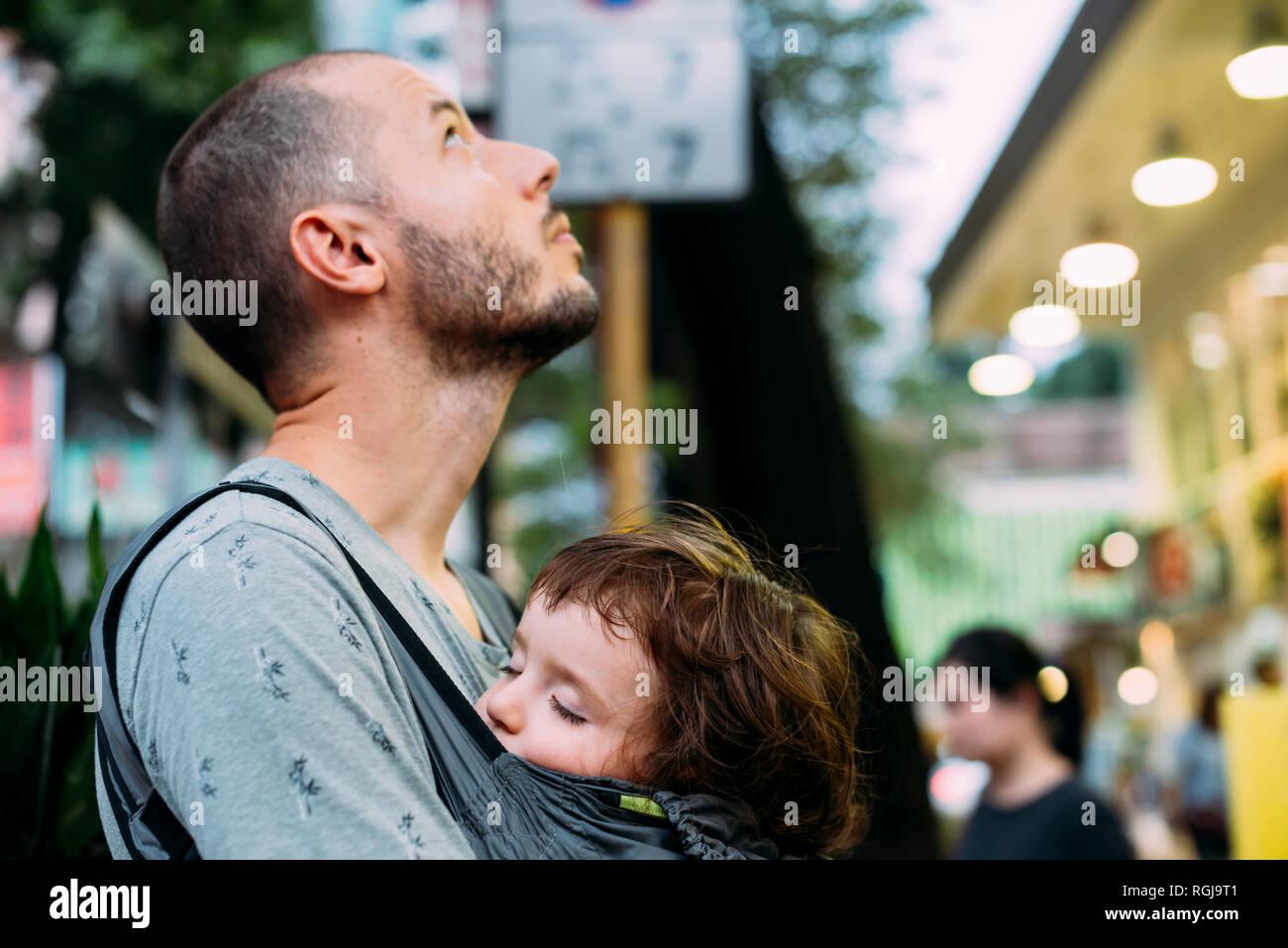 China, Hong Kong, padre viajando con la niña durmiendo en un carrito de bebé Foto de stock