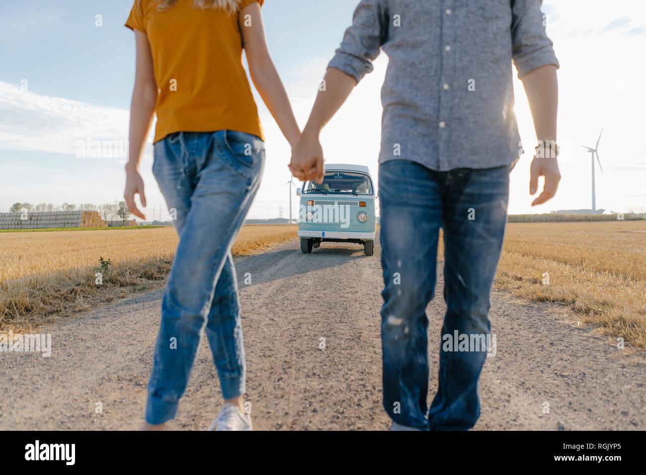 Cerca de la pareja caminando por pista de tierra en autocaravana en paisaje rural Foto de stock