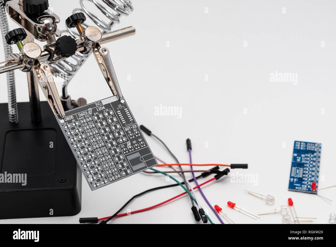 Placa de circuito gris en soldadura ayudando a manos antes del proceso de soldadura tecnológico con LEDs cables y otra placa en el fondo. Imagen De Stock