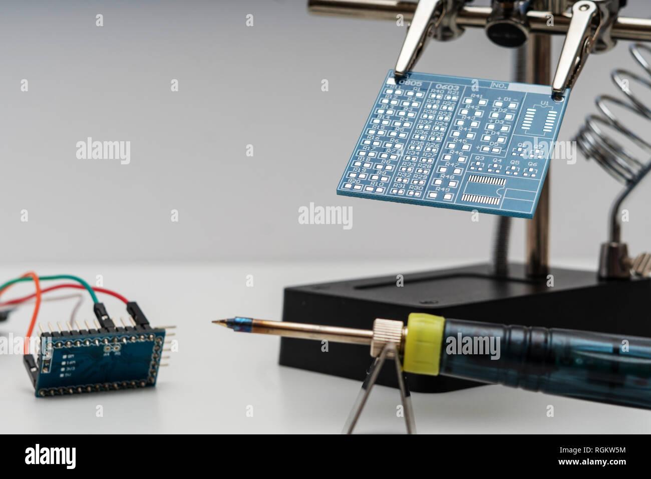 Placa de circuito azul en manos de ayuda tecnológica de soldadura antes de proceso de soldadura con soldador y otra placa de circuito con cables Imagen De Stock