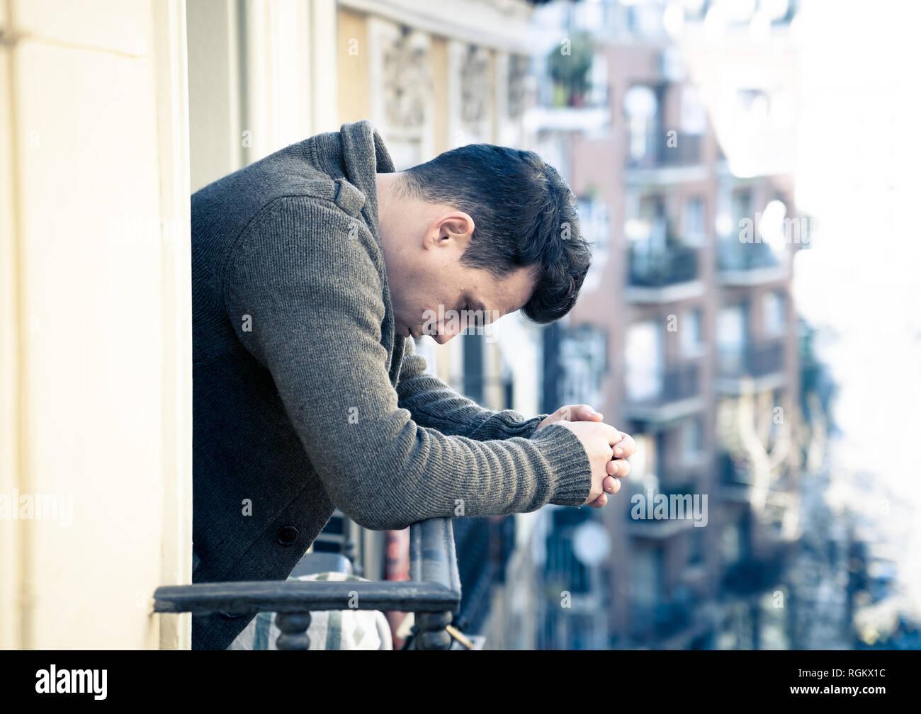 Triste infeliz deprimido joven llorando y desesperado sentimiento suicida,  aislada y sin valor mirando por la calle a casa balcón en personas Depres  Fotografía de stock - Alamy