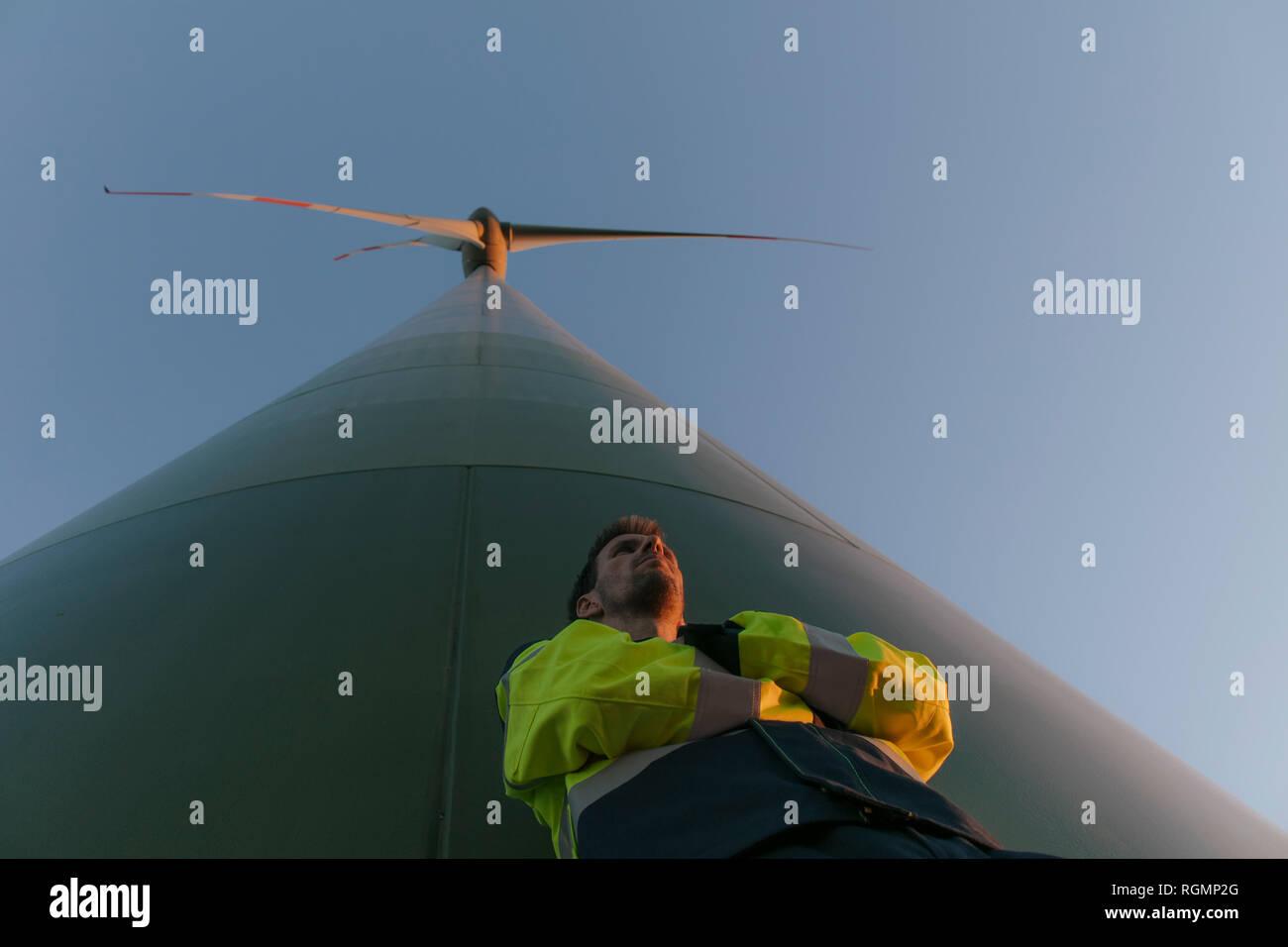 Ángulo de visión baja de un ingeniero de pie en un aerogenerador Foto de stock
