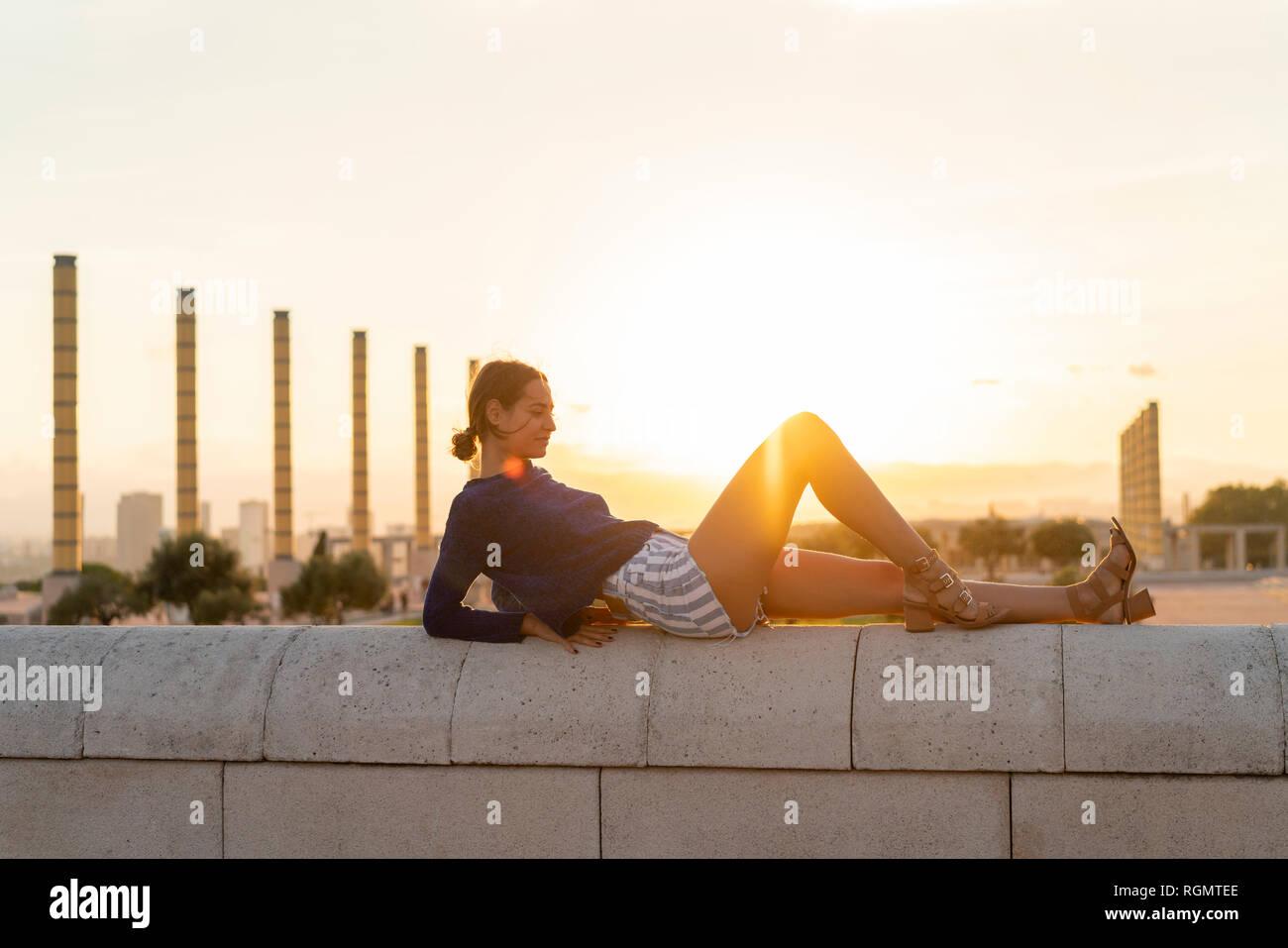 España, Barcelona, Montjuic, joven mujer acostada sobre una pared al atardecer Foto de stock