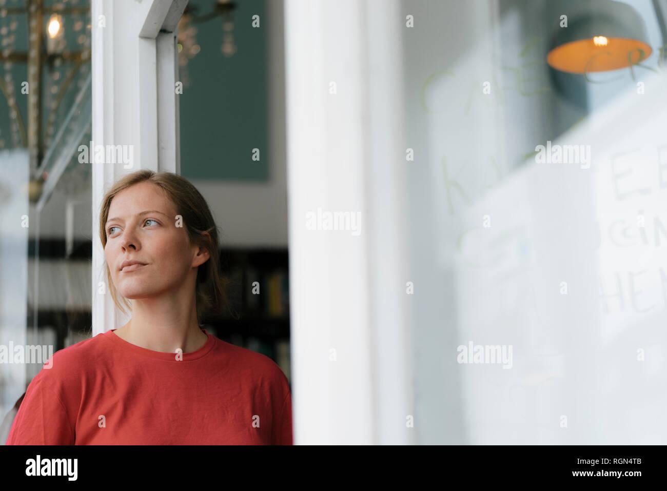 Mujer joven de puerta francesa en un café mirando alrededor Foto de stock