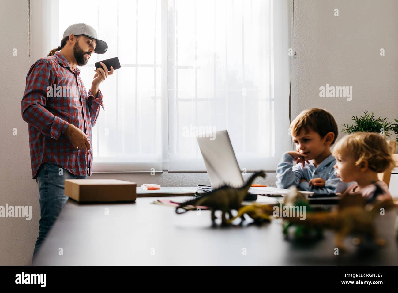 Padre grabando un archivo de audio, mientras los niños están utilizando su ordenador portátil Foto de stock