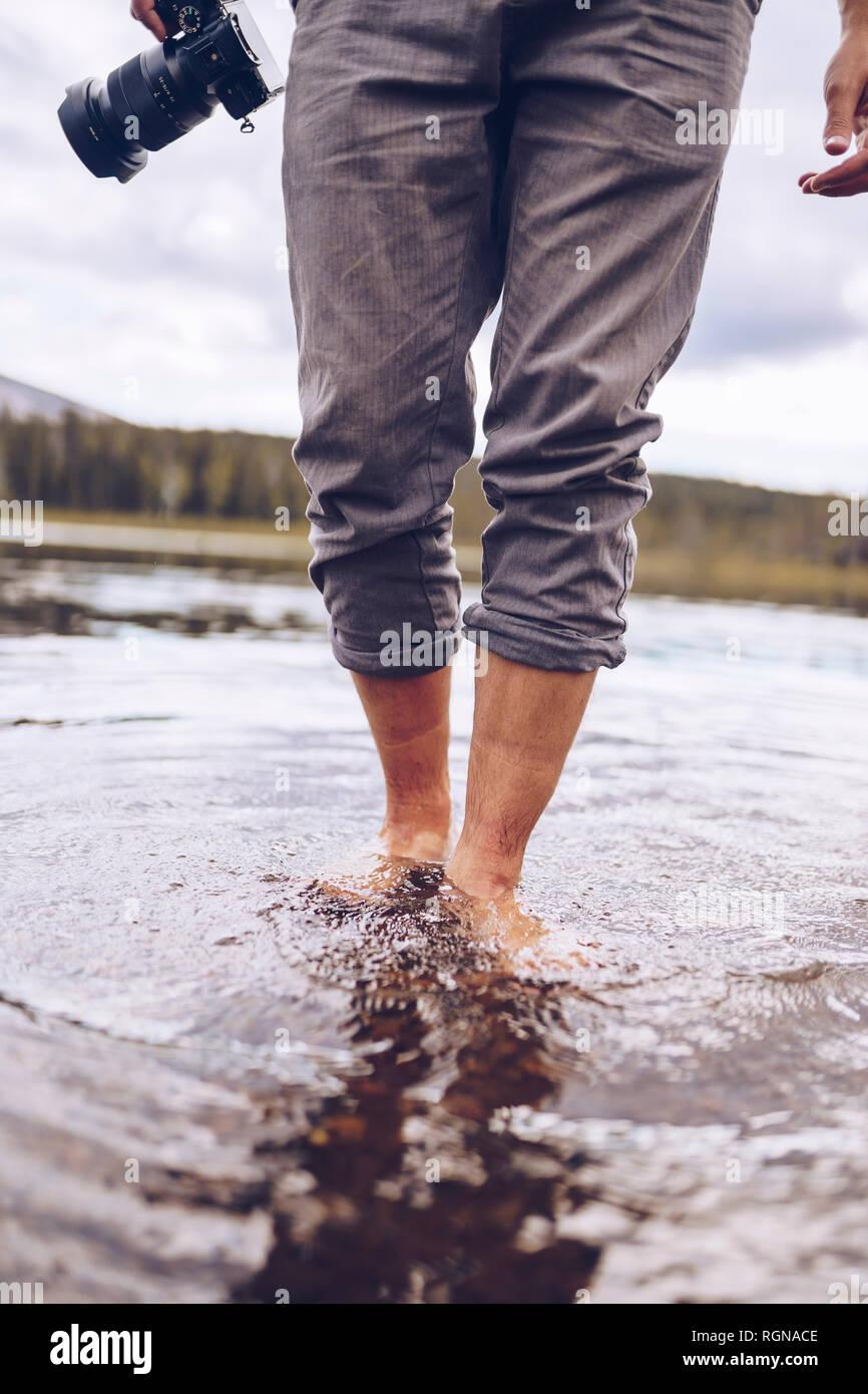 Suecia, Laponia, el hombre con la cámara vadeando en el agua, vista parcial Foto de stock