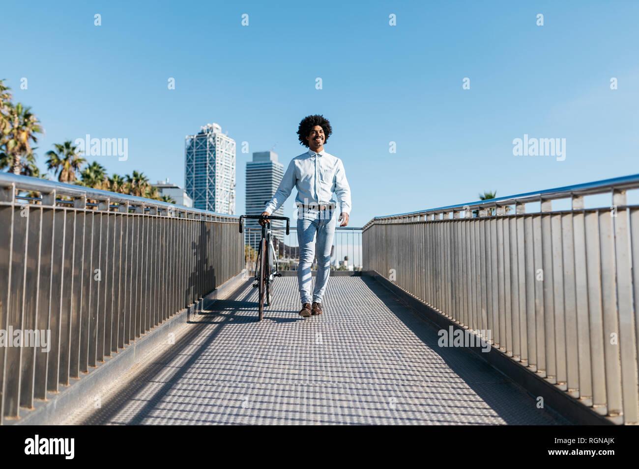 Mitad hombre adulto empujando su bicicleta sobre un puente en la ciudad Foto de stock