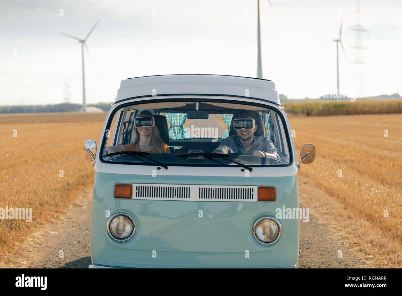 Pareja sonriente vistiendo gafas VR autocaravana conducción en paisaje rural Foto de stock
