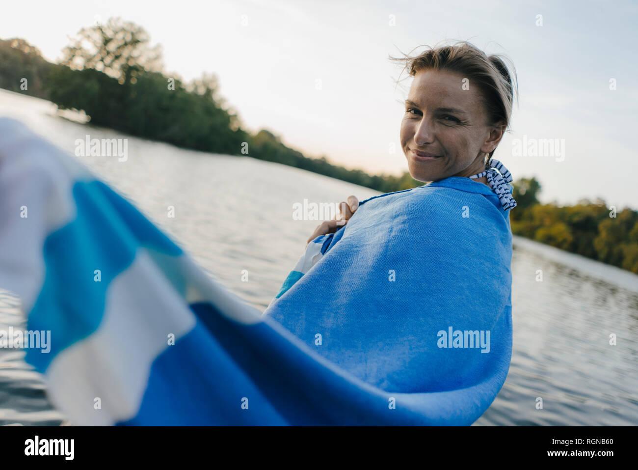 Retrato de mujer sonriente envuelta en una toalla en un lago Foto de stock