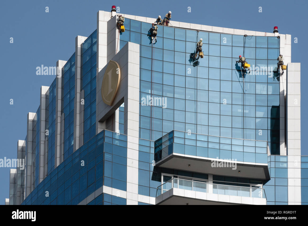 DUBAI, EMIRATOS ÁRABES UNIDOS - 15 de febrero de 2018, hombres: Limpiar la fachada del rascacielos moderno en Dubai, Emiratos Árabes Unidos. Foto de stock