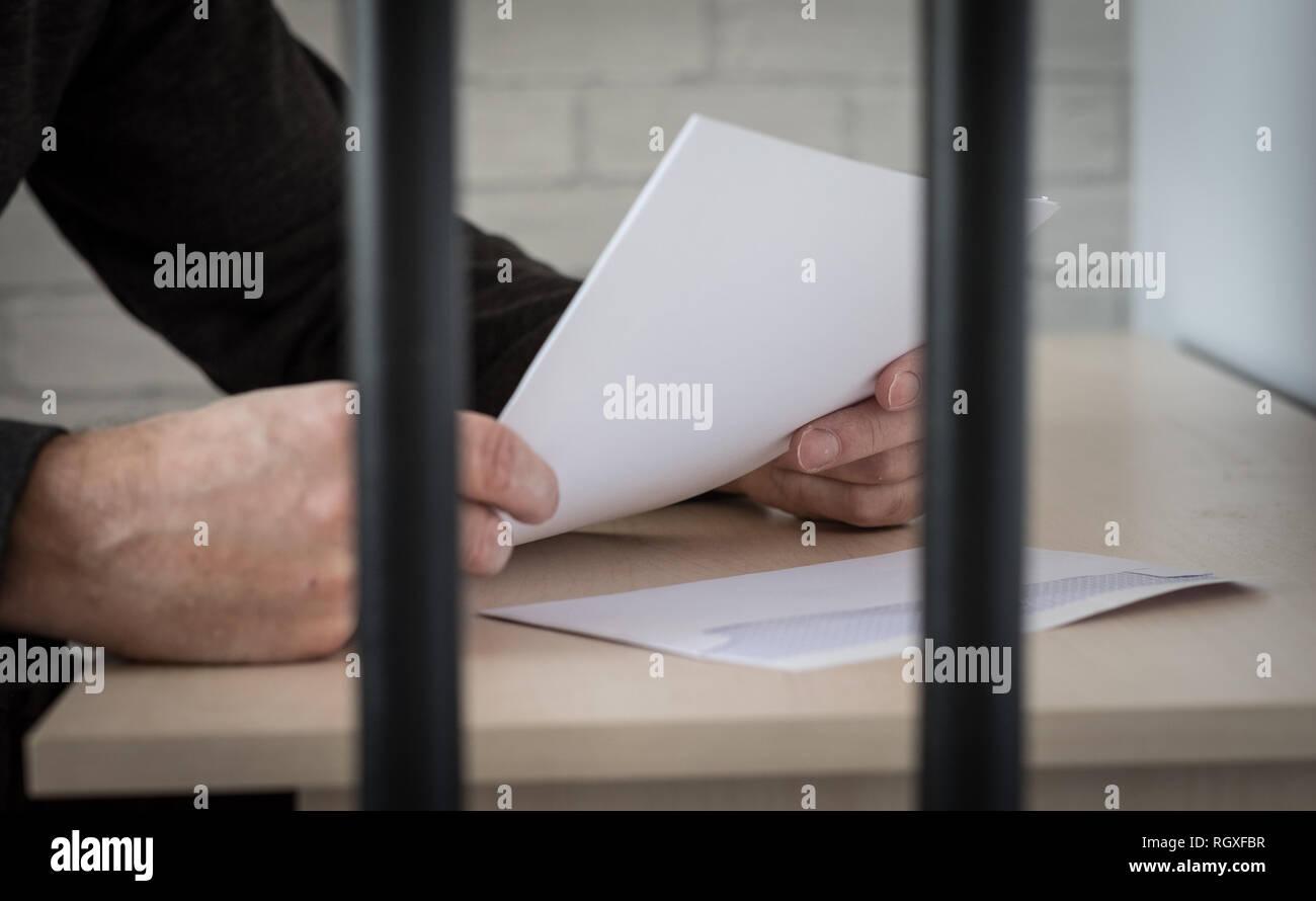 Un prisionero detrás de las rejas leyendo una carta Foto de stock