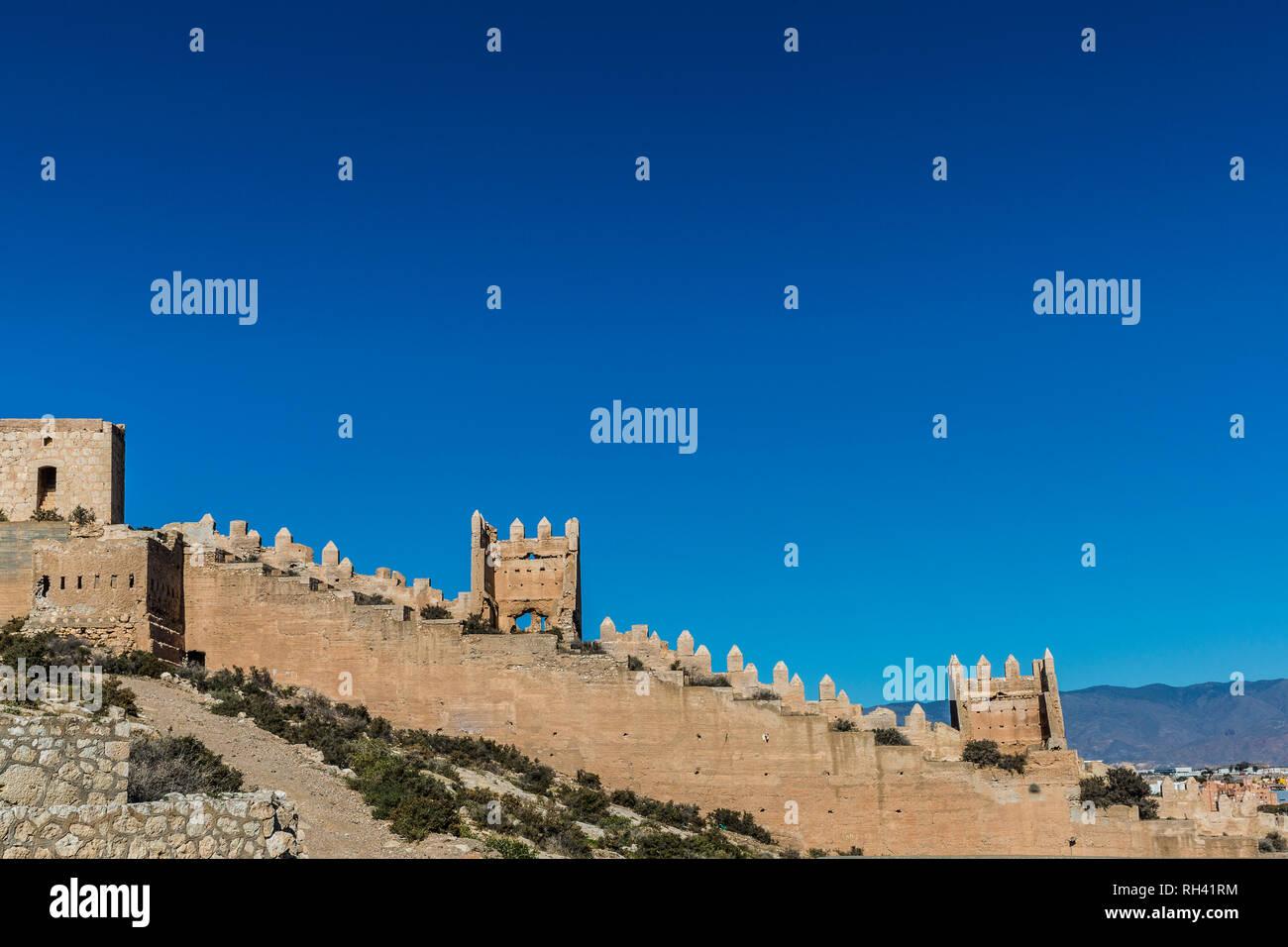 Alcazaba pared sobre una colina en una tierra árida en Almería, España, hermoso día soleado con un cielo azul sin nubes Imagen De Stock