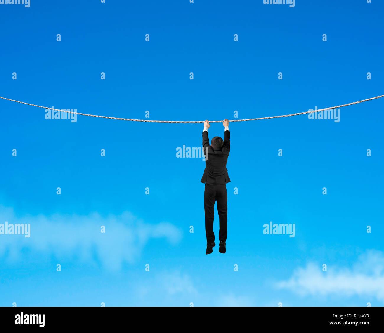 Empresario sosteniendo la cuerda y colgando en el cielo azul Imagen De Stock