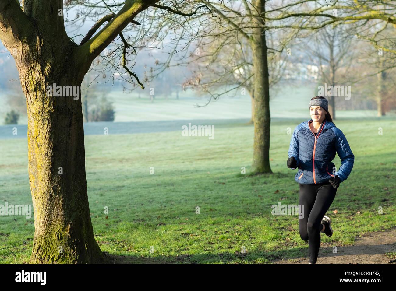Mujer en invierno a primera hora de la mañana recorren Park mantenerse en forma haciendo ejercicio Foto de stock