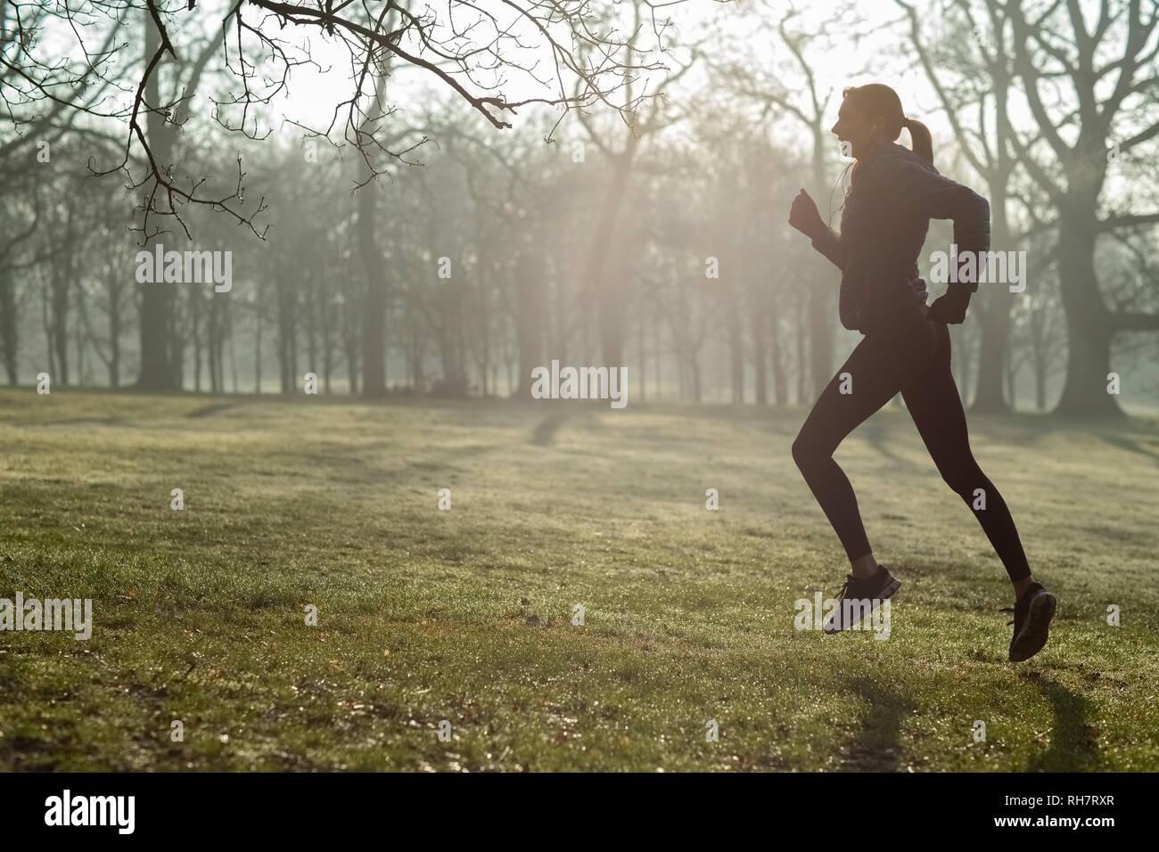 Mujer en invierno temprano por la mañana se ejecute en el mantenimiento del parque Monte escuchando música a través de auriculares. Foto de stock
