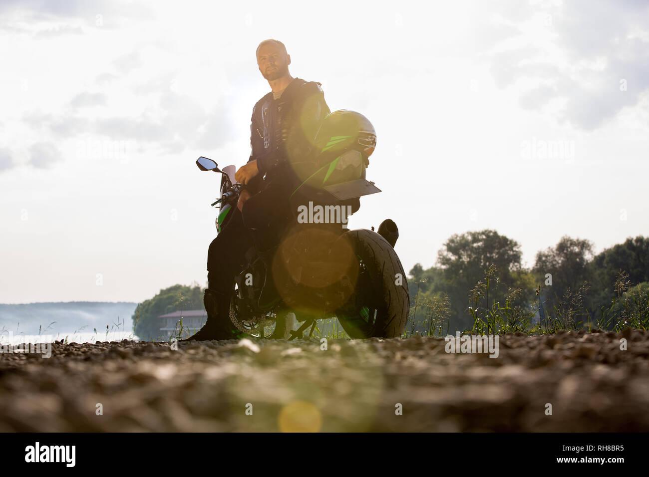 Biker hombre y la motocicleta con el río de fondo, Rider moto viaje en la calle, a la orilla del río, disfrutando de la libertad y un estilo de vida activo. Foto de stock