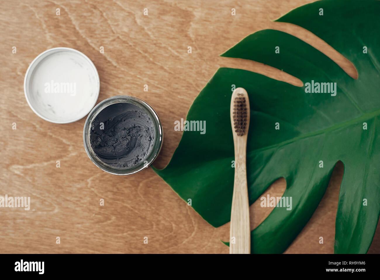 Dentífrico natural el carbón activado en un tarro de vidrio y el bambú, cepillo de madera con fondo verde hoja monstera. Libre de plástico essentials, dientes Foto de stock