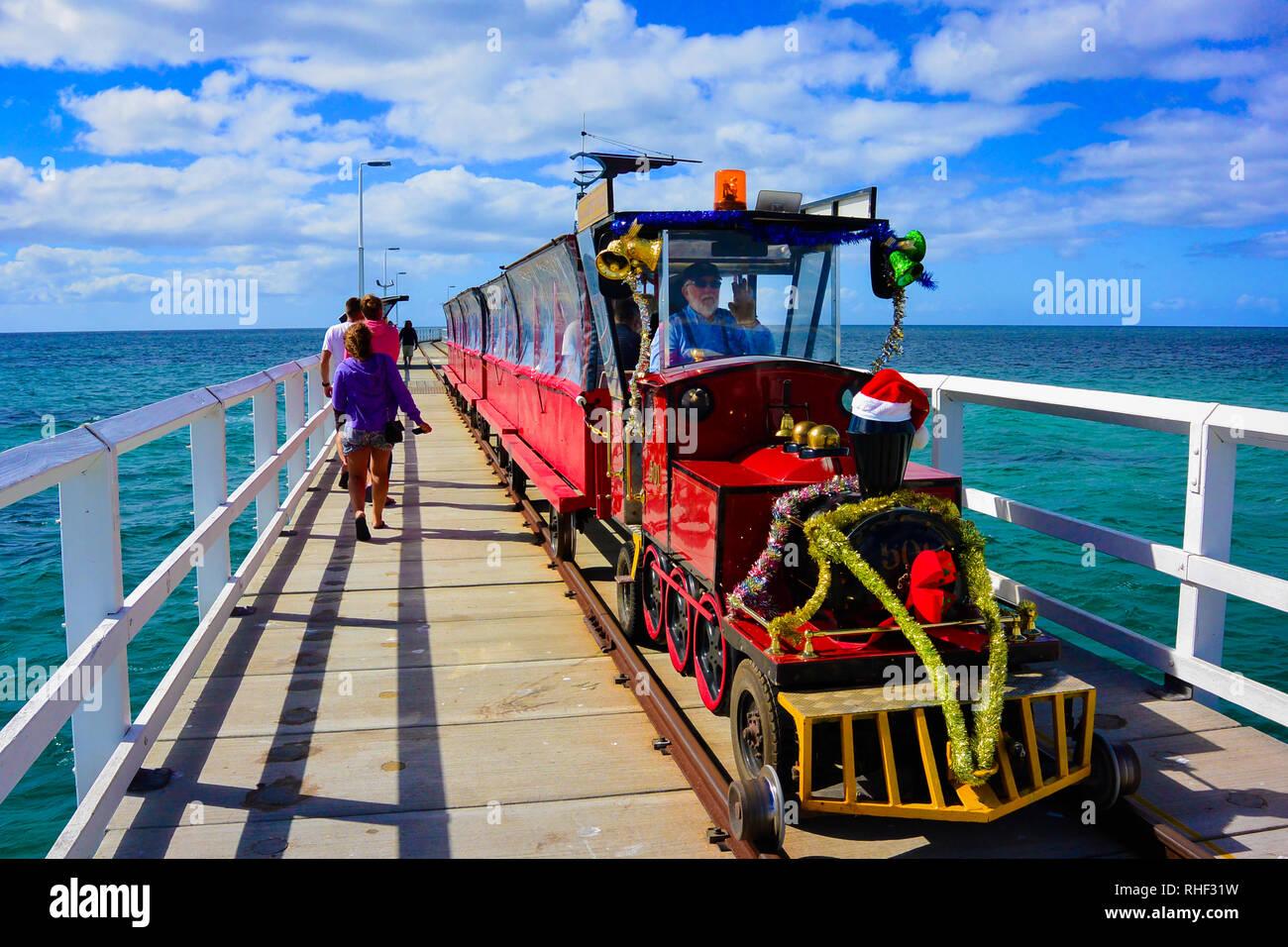 Colorido shot de sorprendente visión de navidad decorado tren el famoso embarcadero de Busselton, Australia Occidental, impulsada por un Santa Claus busca hombre viejo. Imagen De Stock