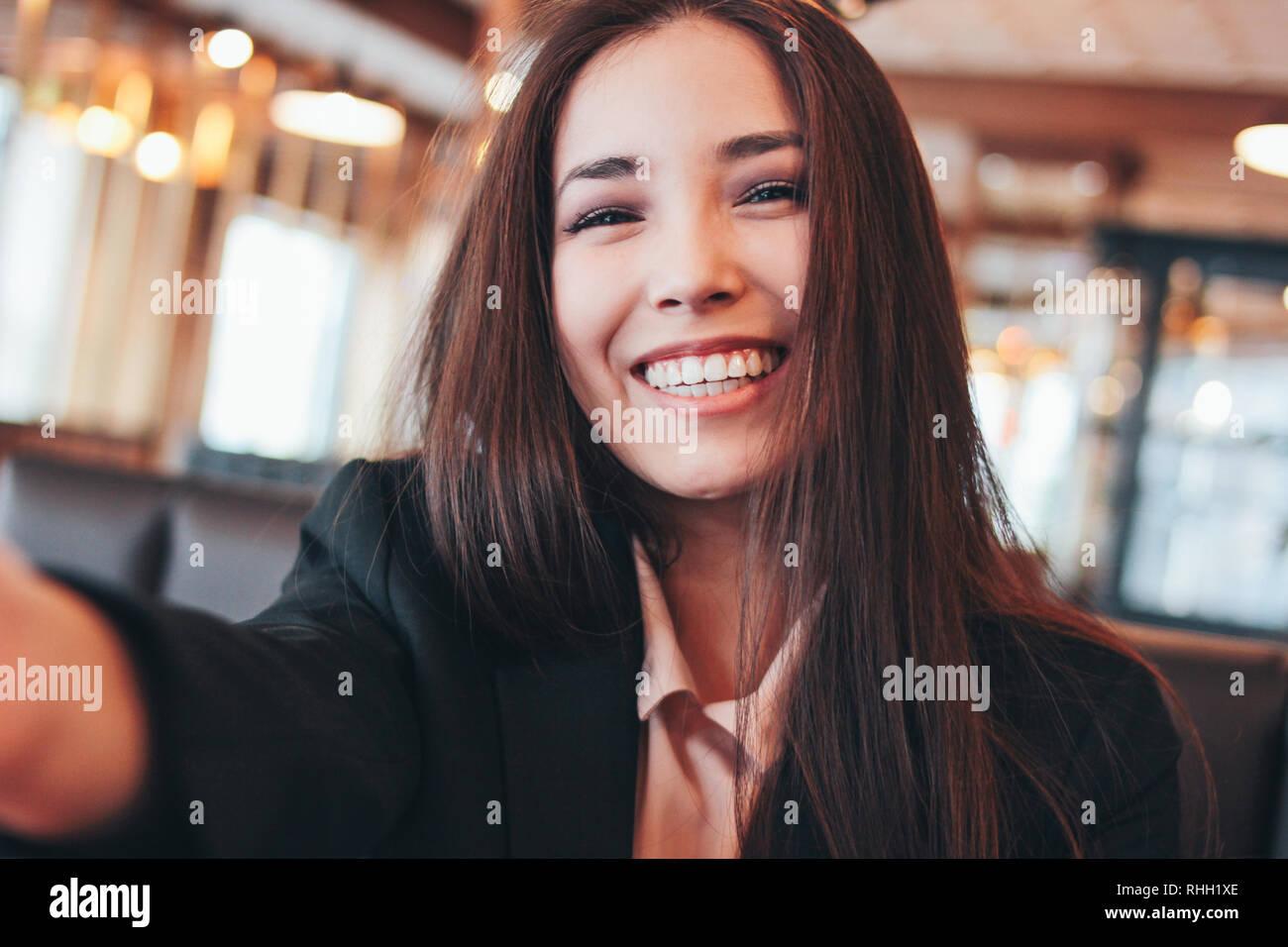 Hermosa morena encantadora chica asiática teniendo selfie sonriente en la cámara frontal en el cafe Foto de stock
