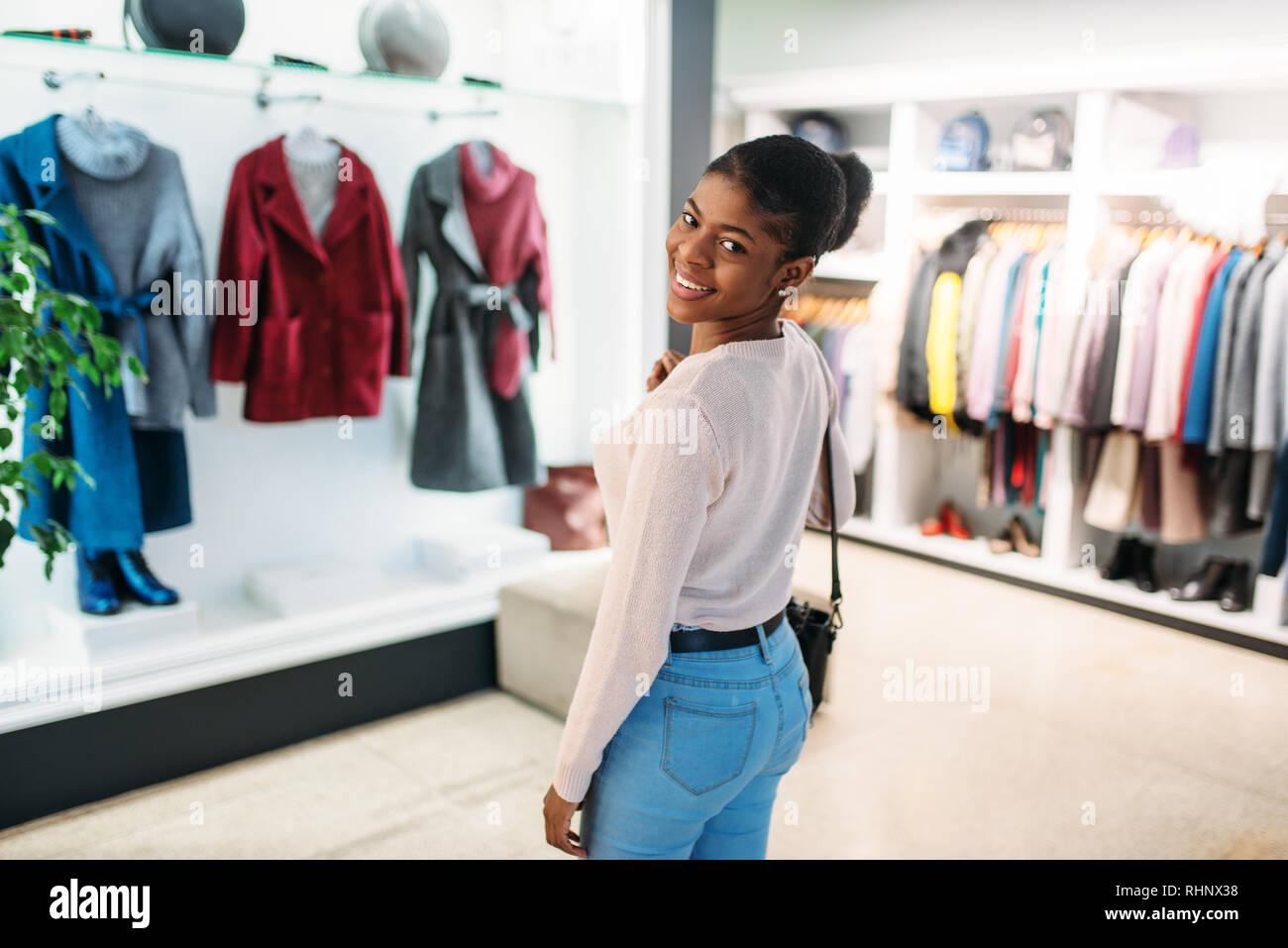 la mejor actitud 9e664 6e35f Atractiva dama negra contra la vitrina con abrigos, compras ...