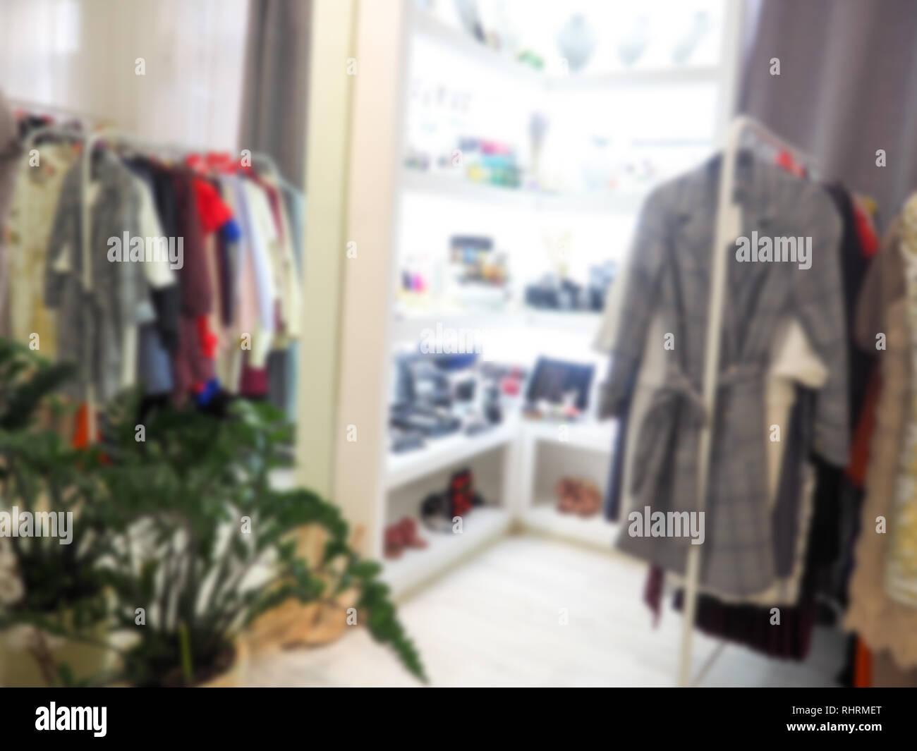 En el colgador de ropa borrosa en la tienda de ropa. Desenfoque desenfoque abstracto y centro comercial del departamento interior de la tienda de fondo. Foto de stock