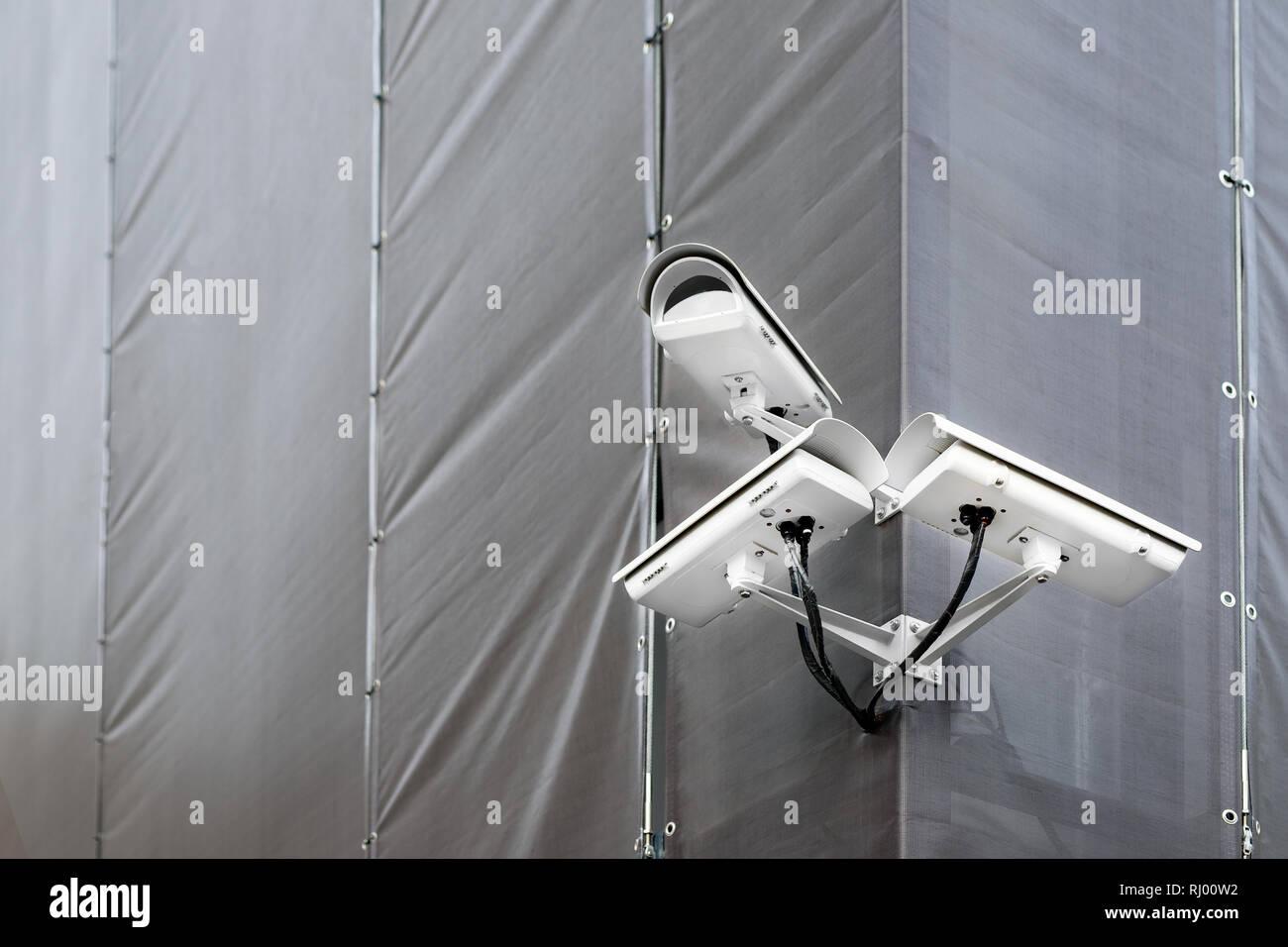 Tres cámaras CCTV en la esquina del edificio en restauración o renovación exterior. Cámaras de seguridad en el muro de la construcción en las calles de la ciudad Foto de stock