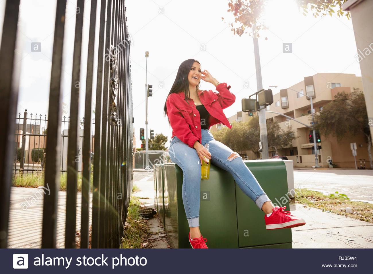 Latinx despreocupada joven sentado en cuadro de electricidad Imagen De Stock