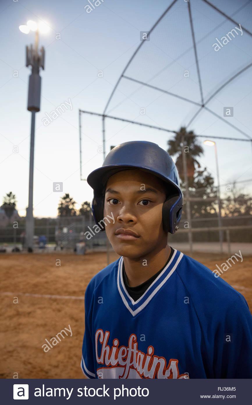 Retrato seguro, determinado jugador de béisbol en el campo de noche Imagen De Stock