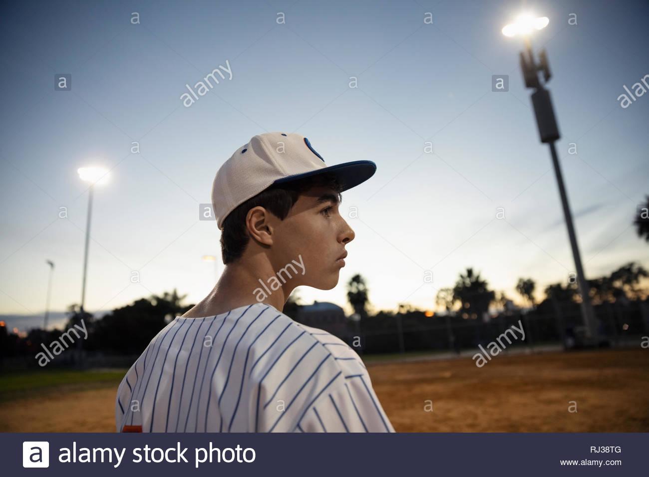 Jugador de béisbol Latinx determinado en el campo de noche Imagen De Stock