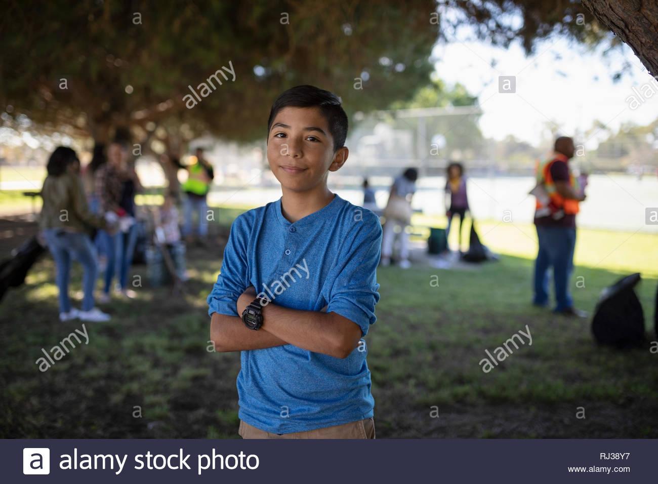 Retrato seguros Latinx boy voluntariado, parque de limpieza Foto de stock