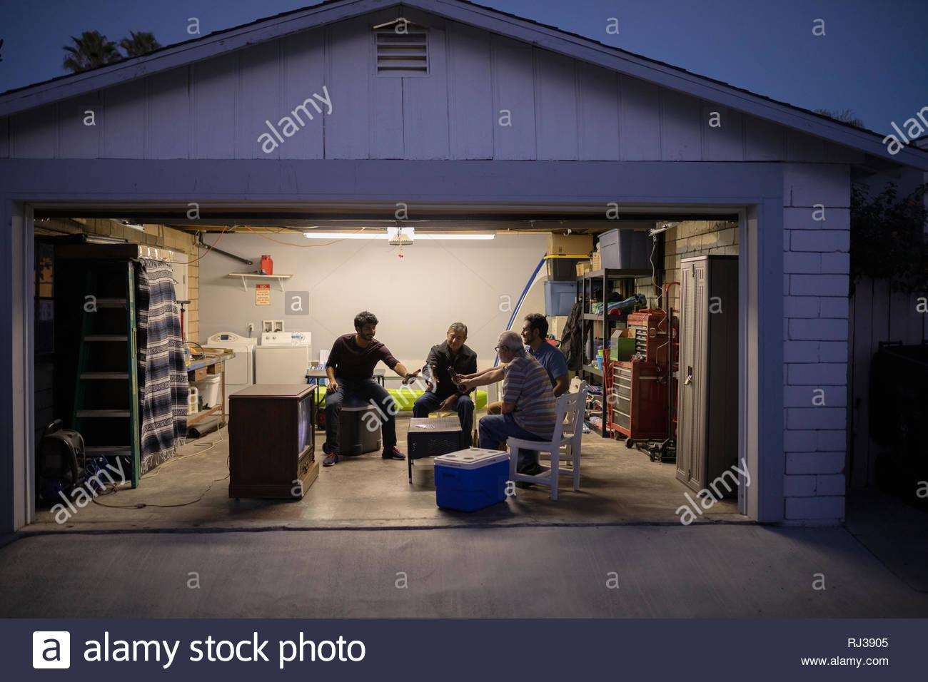 Los hombres Latinx bebiendo cerveza, ver deportes en la televisión en el garaje durante la noche Imagen De Stock
