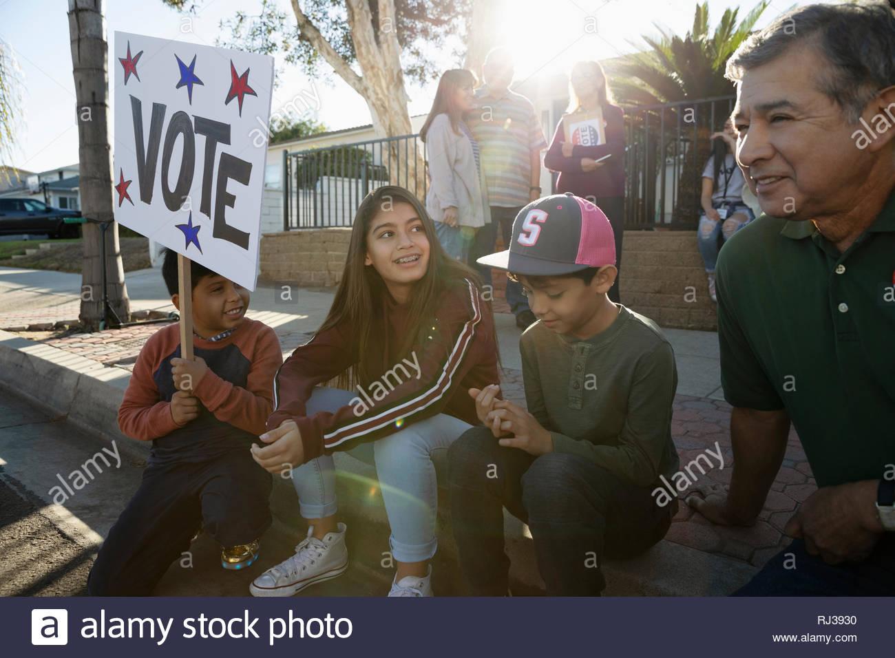 Latinx abuelo y nietos la captación de electores en la acera Imagen De Stock