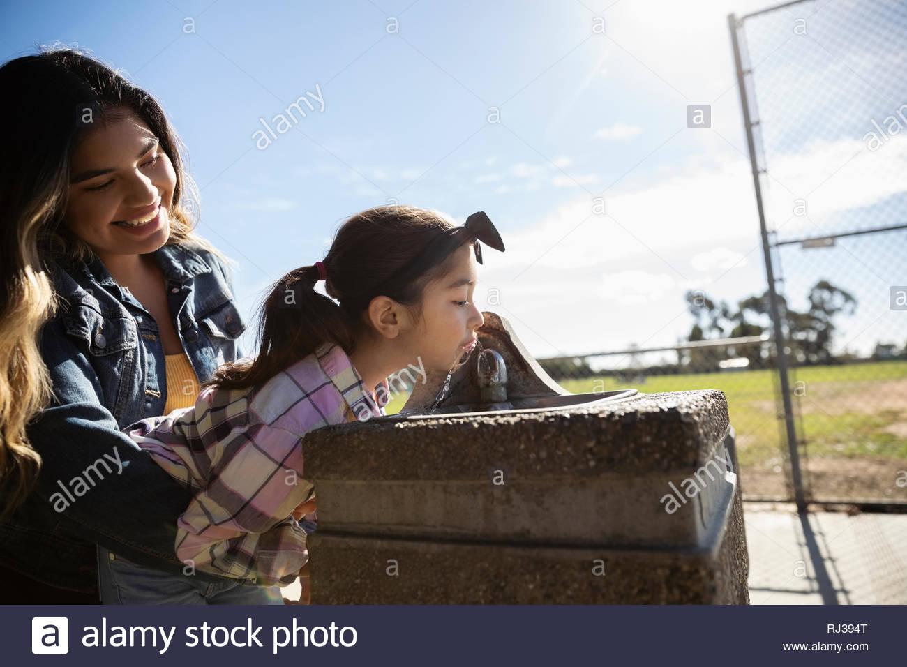 Chica Latinx hermana de elevación a la fuente de agua potable en el parque soleado Imagen De Stock