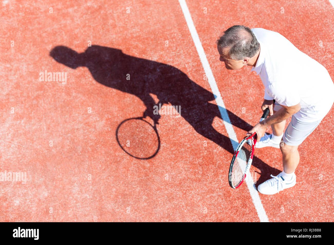 La longitud total del hombre senior jugando tenis en rojo corte durante el fin de semana de verano Foto de stock
