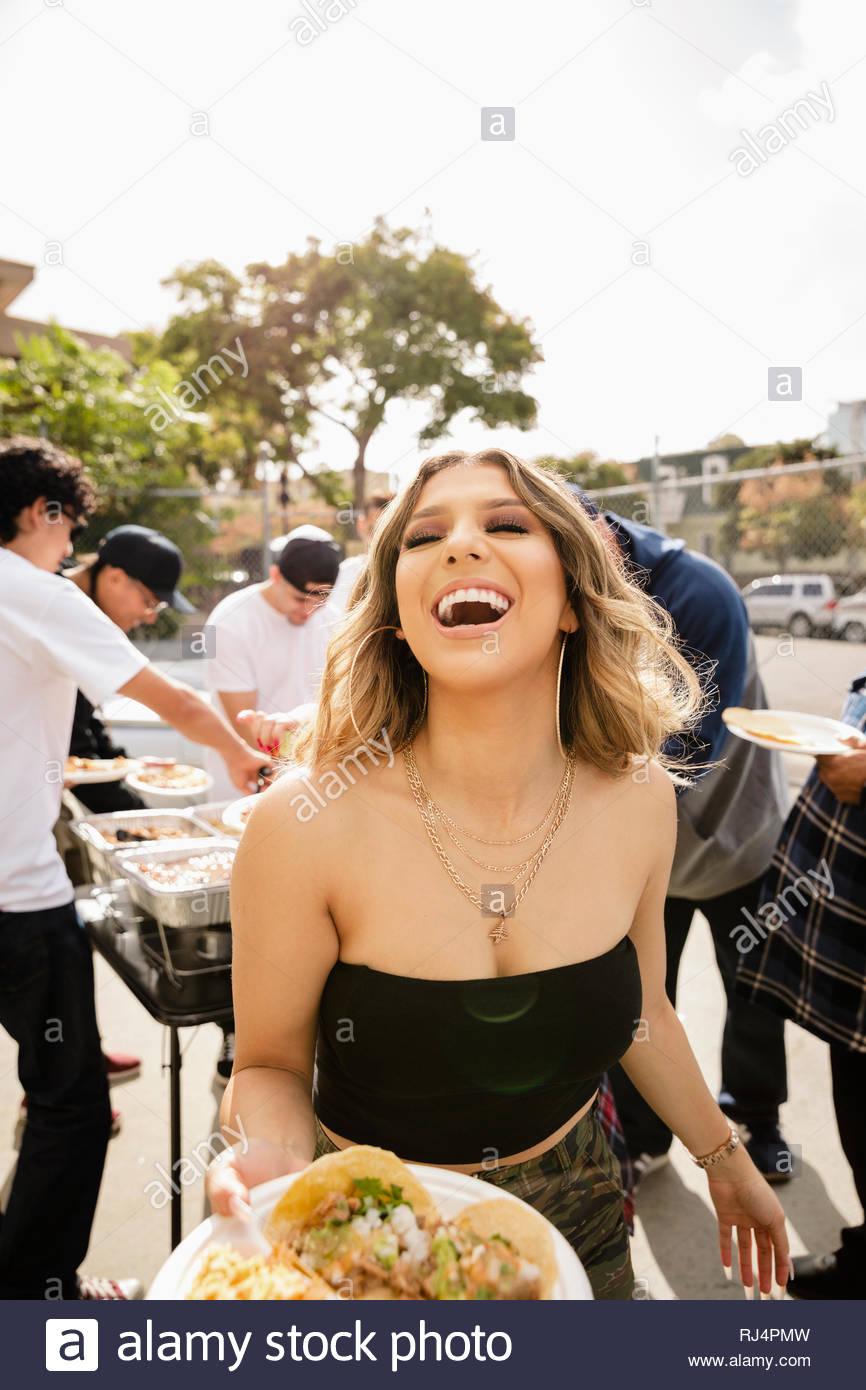 Retrato riendo, carefree Latinx mujer disfrutando de taco el almuerzo en el estacionamiento Imagen De Stock