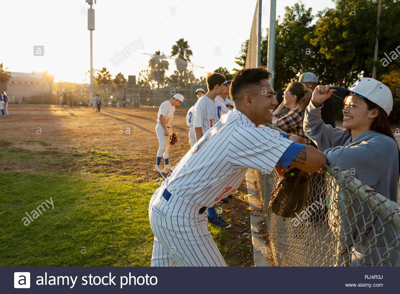Jugador de béisbol feliz hablando a la novia en la regleta Imagen De Stock
