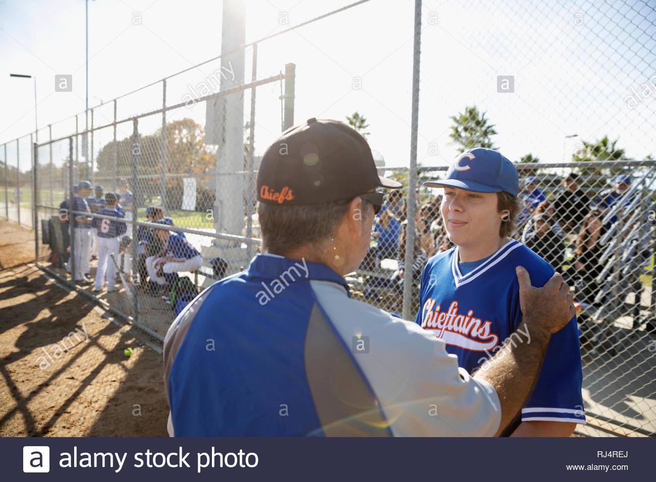 Autobús hablando con el jugador de béisbol en el campo soleado Imagen De Stock