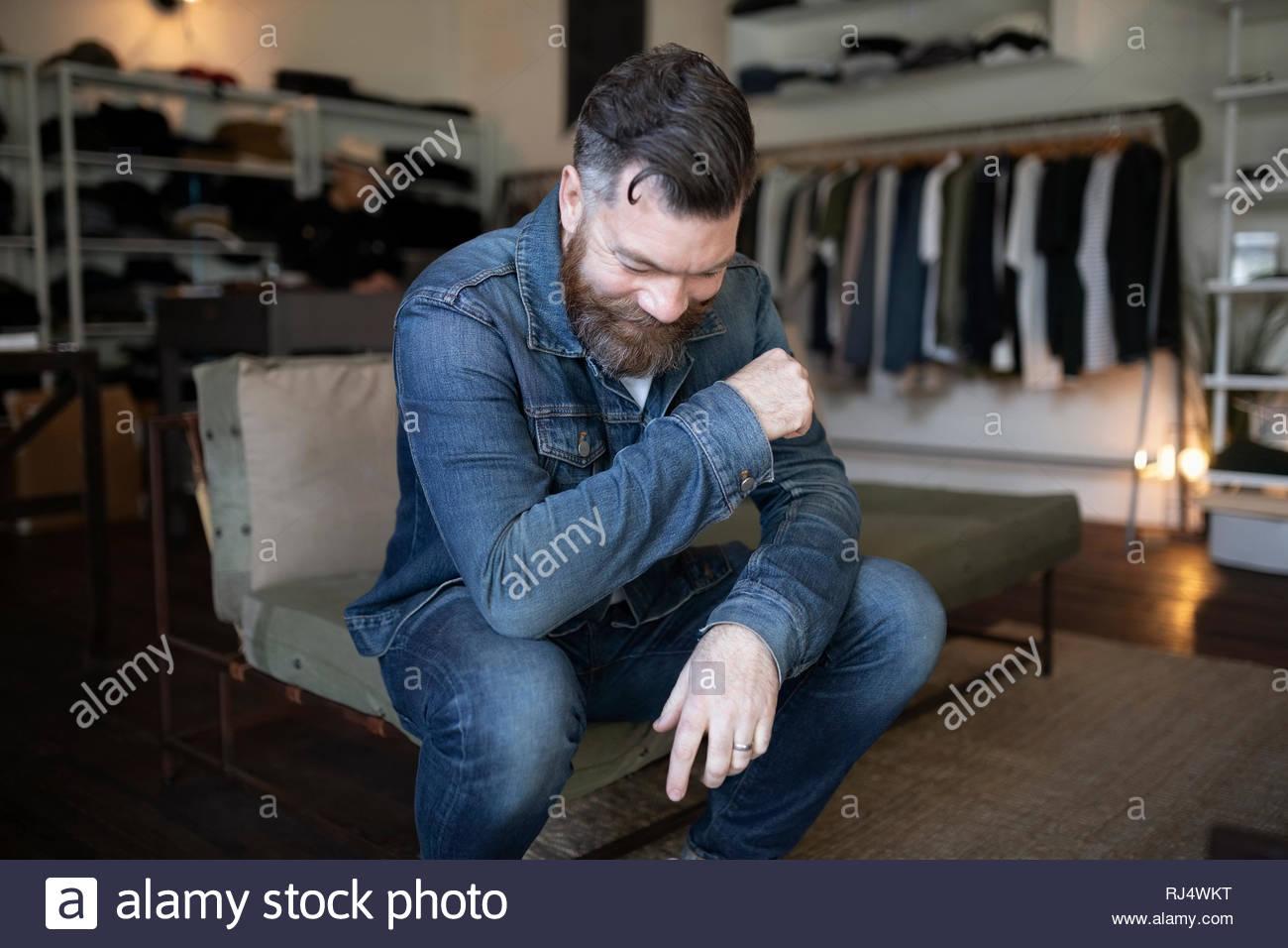 Hombre sonriendo con barba en ropa tienda de ropa Foto de stock