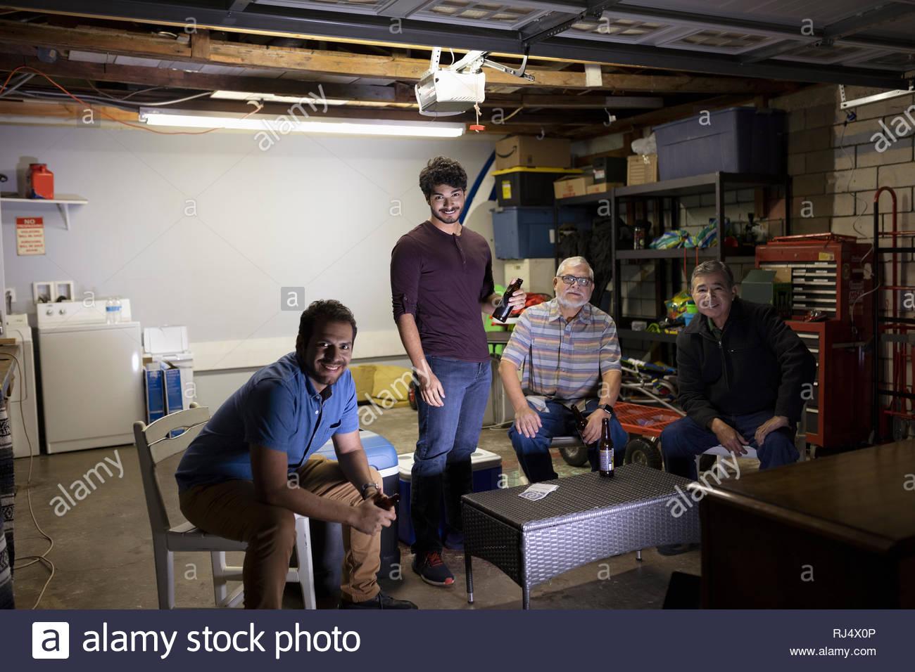 Retrato Latinx hombres viendo deportes en la televisión en el garaje Imagen De Stock