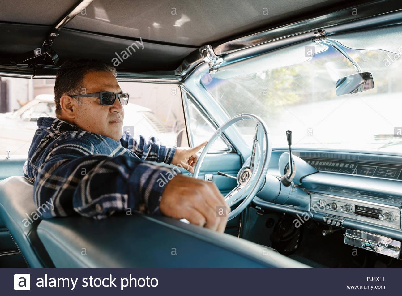 Hombre Latinx conducir coches antiguos Imagen De Stock